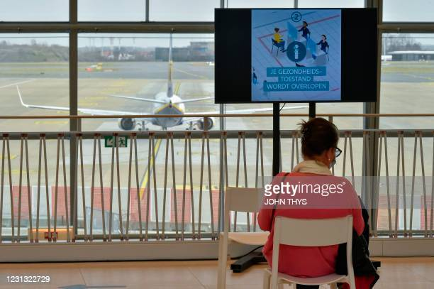Woman sits in a wainting area before receiving an injection of the Covid-19 vaccine on the opening day of the vaccination centre at the Zaventem...