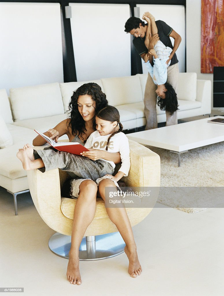 Woman Sits in an Armchair With Her Daughter on Her Lap, Reading a Book to Her, Dad and Sister in the Background : Stock Photo