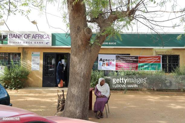 A woman sits in front of a Bank of Africa branch on December 20 2017 in Niamey / AFP PHOTO / LUDOVIC MARIN
