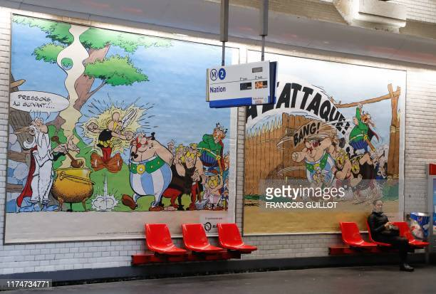 A woman sits in front of a drawing especially designed to commemorate the 60th anniversary of France's famous comic characters Asterix and Obelix on...