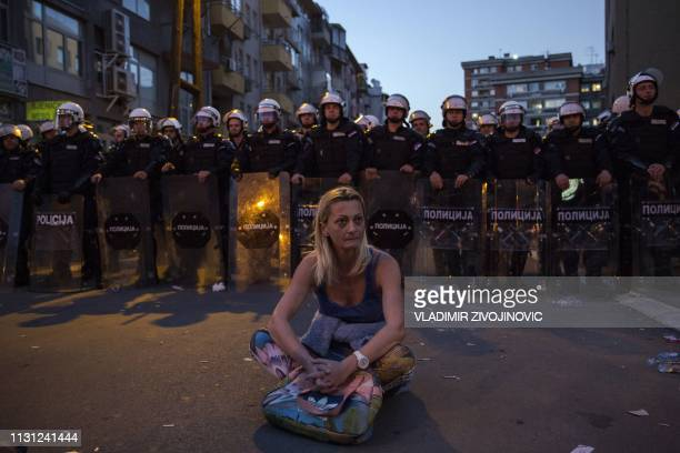 TOPSHOT A woman sits in front of a riot police cordon after a standoff during a demonstration against Serbian President Aleksandar Vucic outside the...