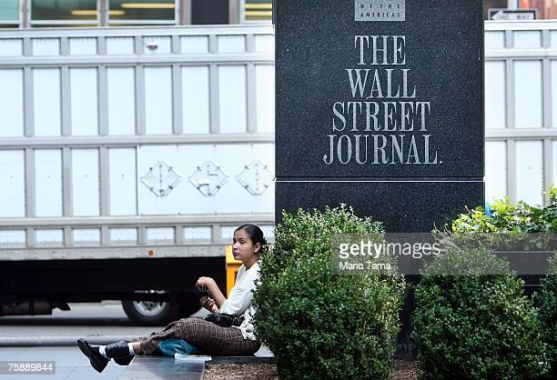 A woman sits in front of a sign outside a Wall Street Journal office on Avenue of the Americas July 31 2007 in New York City Rupert Murdoch's News...