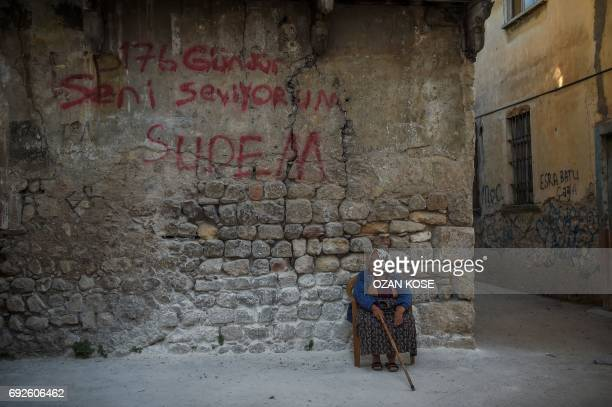 TOPSHOT A woman sits in front of a wall graffiti reading 'I love you since 176 days' at the historical streets of Antakya on June 5 2017 in Hatay /...
