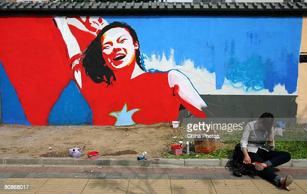 Woman sits in front of a wall with colorful graffiti during an activity to celebrate the upcoming 100-day-countdown to the 2008 Beijing Olympics,...