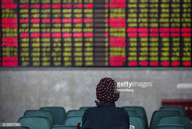 A woman sits in front of an electronic board displaying share prices at a securities exchange house in Shanghai China on Monday Feb 15 2015 China's...
