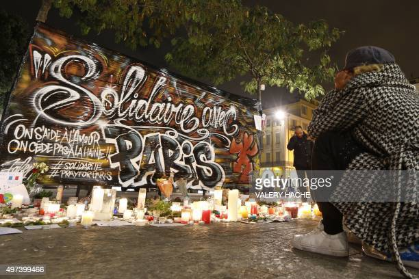 A woman sits in front of candles and flowers at a makeshift memorial on November 16 2015 in Nice in tribute to November 13 attacks in Paris Islamic...
