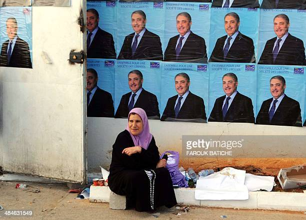 Woman sits in front of electoral posters of independent candidate to Algeria's presidential election Ali Benflis, on the last day of the electoral...