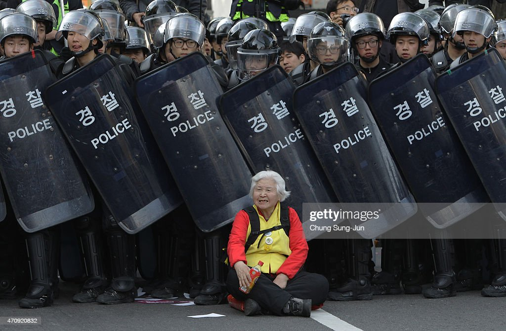 A woman sits in front of riot police blocking the road to protect protesters during the anti-government protest on April 24, 2015 in Seoul, South Korea. Korean Confederation of Trade Unions (KCTU) went on a general strike in protest against the South Korean government's policy, including reformation of the labor market and public pension system. The rally was also joined by other civic groups in Seoul and families of Sewol accident victims.