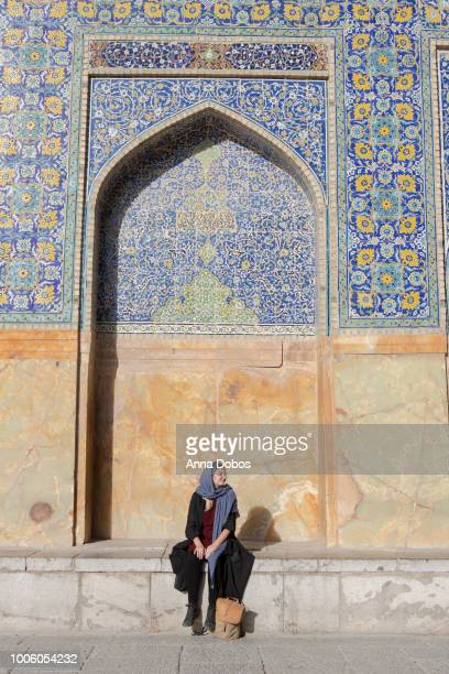 woman sits in front of tiled wall in naqsh-e jahan square - isfahan stock-fotos und bilder