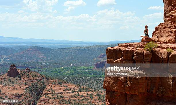 Woman sits in gratitude on Cathedral Rock in Sedona, Arizona.