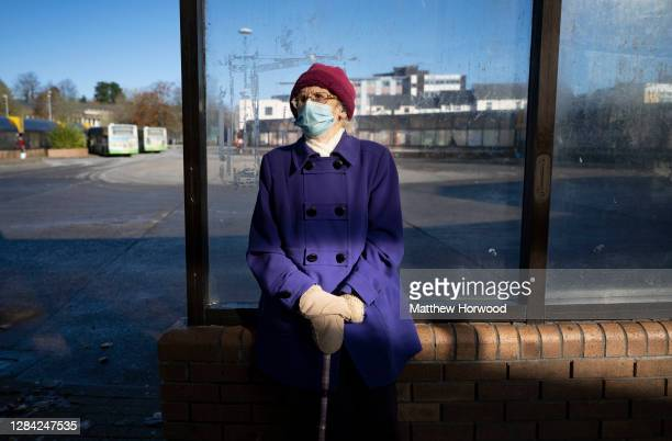 Woman sits in Merthyr bus station wearing a surgical face mask on November 6, 2020 in Merthyr Tydfil, Wales. Merthyr Tydfil, with 741 cases per...