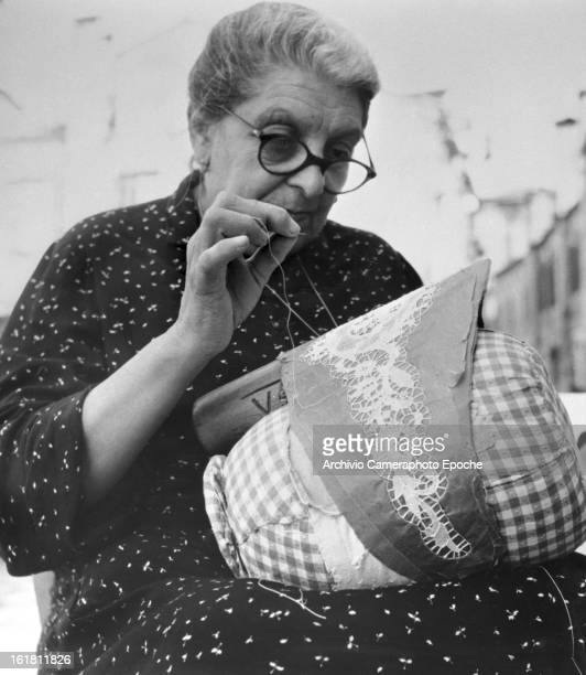 A woman sits in the courtyard making lace Burano Venice 1949