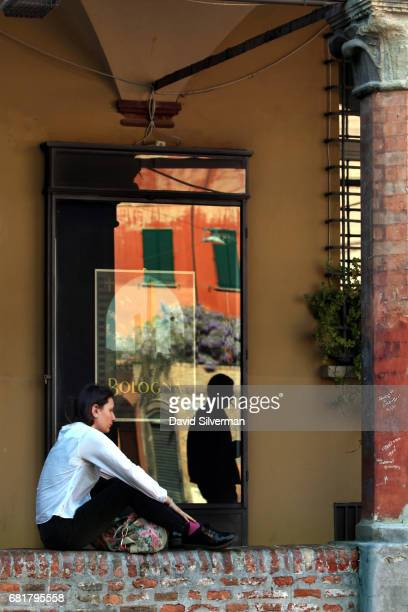 A woman sits in the shade of one of the city's famous covered arcades in Piazza Santo Stefano on March 31 2017 in central Bologna Italy The porticoes...