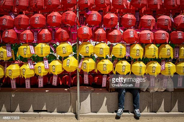 Woman sits in the shade underneath lines of lanterns after the Vesak Buddhist Ceremony celebrating Buddha's birth at the Jogyesa Temple on May 6,...