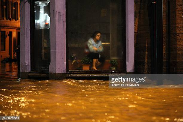 TOPSHOT A woman sits inside a Chinese Restaurant watching floodwater race by the window in Dumfries southern Scotland on December 30 2015 after heavy...
