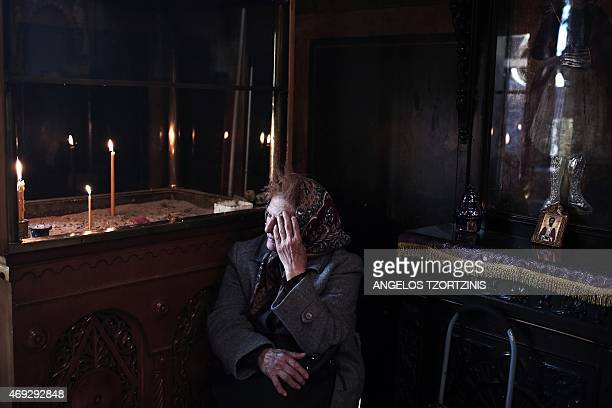 A woman sits inside a church during Orthodox Easter celebrations in Athens on April 11 2015 Millions of Greeks flock to churches around the country...