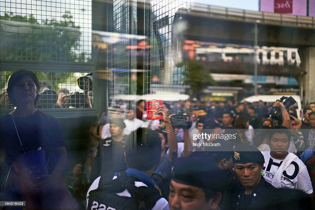 A woman (L) sits inside a police van after being detained by police for holding an anti-coup message on May 29, 2014 in Bangkok, Thailand. The police and military shut down one of Bangkok's central roundabouts today after four consecutive days of anti-coup protests in the area. Under current martial law in Thailand, it is illegal for public gatherings of more than five people and it is also illegal to protest against the military's intervention.