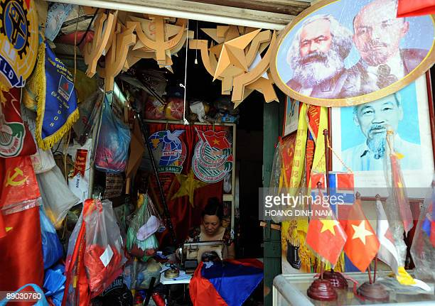 A woman sits making flags with a sewing machine in her tinny shop selling political decorative items including flags banners communist signs and...