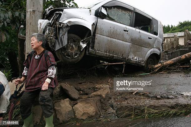 Woman sits near a damaged vehicle after heavy rain and a mudslide hit Okaya city July 20, 2006 in Nagano, Japan. Torrential rains in central and...