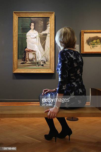 A woman sits near a painting by Edouard Manet entitled 'Portrait of Mademoiselle Claus' from 1868 in the Ashmolean Museum on February 24 2012 in...