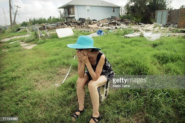 A woman sits near the repaired levee wall which was breached during Hurricane Katrina's aftermath while attending the Great Flood memorial ceremony...