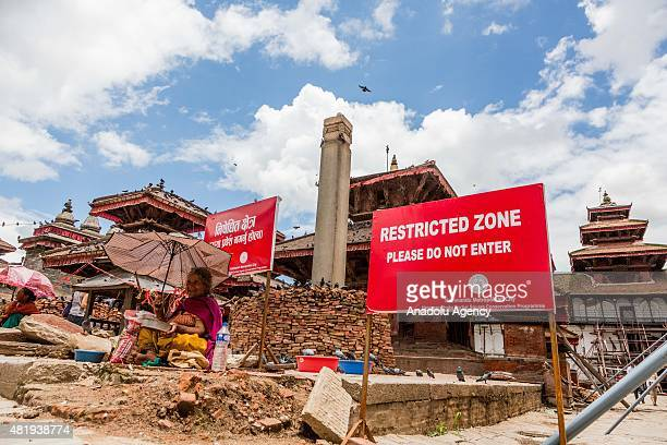 Woman sits next to a 'danger' sign while selling bird seed to devotees at the destroyed ancient temples in Durbar sqaure, Kathmandu on July 25, 2015....
