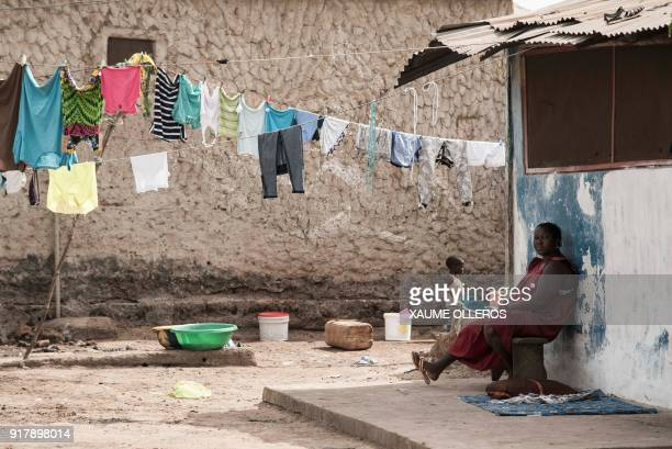 A woman sits next to a line of wash in the Mindara neighbourhood in Bissau on Mardi Gras on February 13 2018 / AFP PHOTO / Xaume Olleros