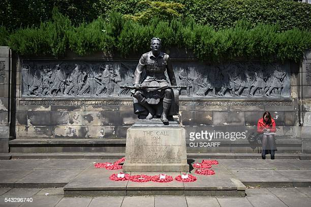 A woman sits next to a monument commemorating the First World War in Princes Street Gardens in the city centre of Edinburgh Scotland on June 27 2016...