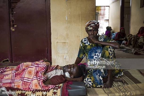 A woman sits next to a wounded civilian waiting for care at Bangui's hospital on December 10 2013 French President Francois Hollande was expected...