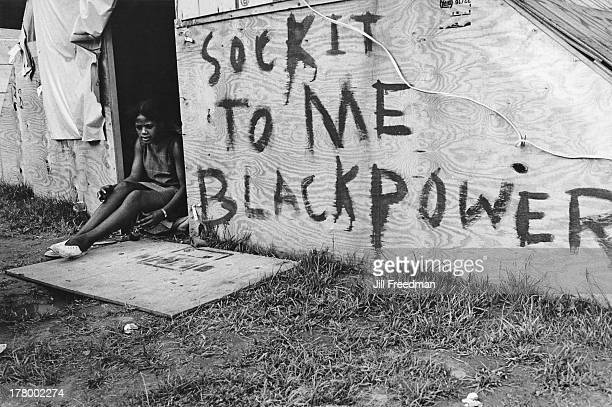 A woman sits next to graffiti on a shelter reading 'Sock It To Me Black Power' in Resurrection City a three thousand person tent city on the...