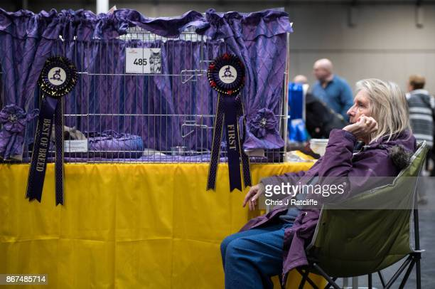 A woman sits next to her cat in its cage during the Supreme Cat Show on October 28 2017 in Birmingham England The oneday Supreme Cat Show is one of...