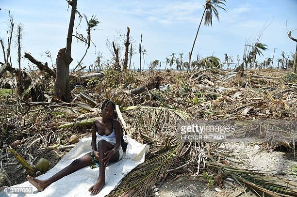 TOPSHOT A woman sits next to her destroyed house in Les Cayes Haiti on October 10 following the passage of Hurricane Matthew Haiti faces a...