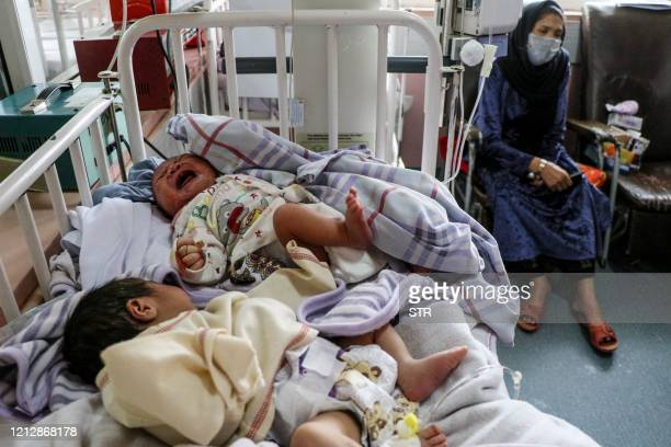 TOPSHOT A woman sits next to newborn babies who lost their mothers following a suicide attack in a maternity hospital in Kabul on May 13 2020 The...