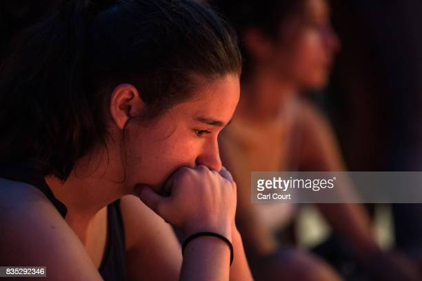 A woman sits next to tributes on Las Ramblas near the scene yesterday's terrorist attack on August 18 2017 in Barcelona Spain Fourteen people were...