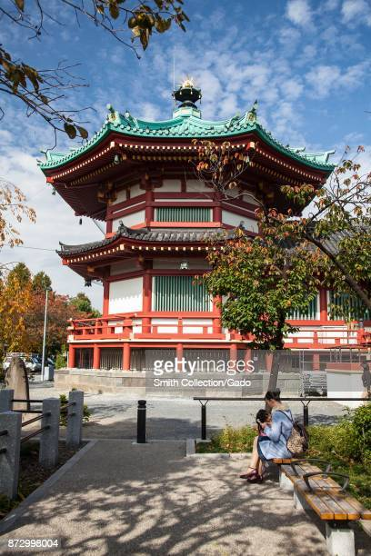 A woman sits on a bench in front of the Bentendo Temple on a sunny day in Ueno Park Ueno District Taito Tokyo Japan November 2017