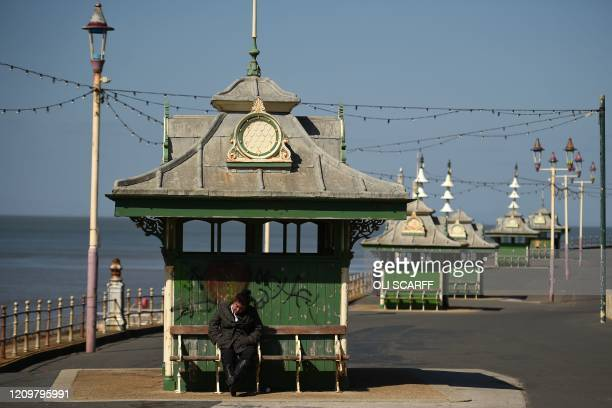 Woman sits on a bench in the spring sunshine on the coast in Blackpool, north-west England on April 13 during the nationwide lockdown to combat the...