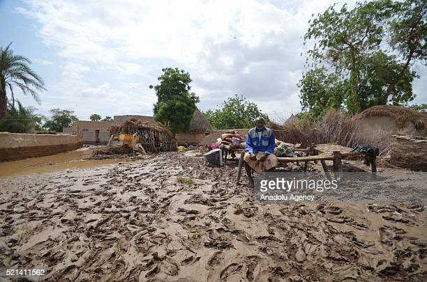 A woman sits on a bench near a muddy area after a day long torrential rain caused flood in Sana'a Yemen on April 15 2016
