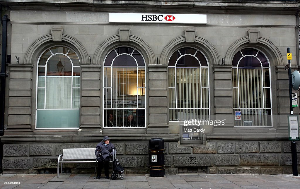 A woman sits on a bench outside a branch of HSBC on March 3 2008 in Wells, United Kingdom. HSBC, the UK's largest bank, has said it has made a 8.7bn GBP loss, after the decline in the US housing market hit the value of its loans. The bank's losses are said to be the biggest write-down of the UK's big five because it has a lot of business and operations in the USA, however its annual profits still rose 10 percent to 12.2bn GBP, up from the year before.