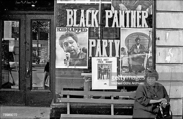 Woman sits on a bench outside the Black Panther office in Harlem circa 1970 in New York City, NY. Pictured in the window are Panther founders Huey P....
