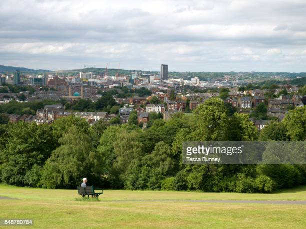 Woman sits on a bench over looking the city at Meersbrook Park on 25 June 2017 in Sheffield, United Kingdom