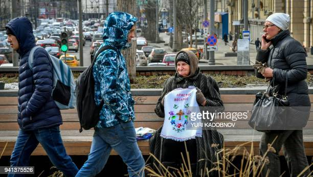 A woman sits on a bench selling home made Easter towels crossstiched with the words Christ is Risen days ahead of Russian Orthodox Easter...