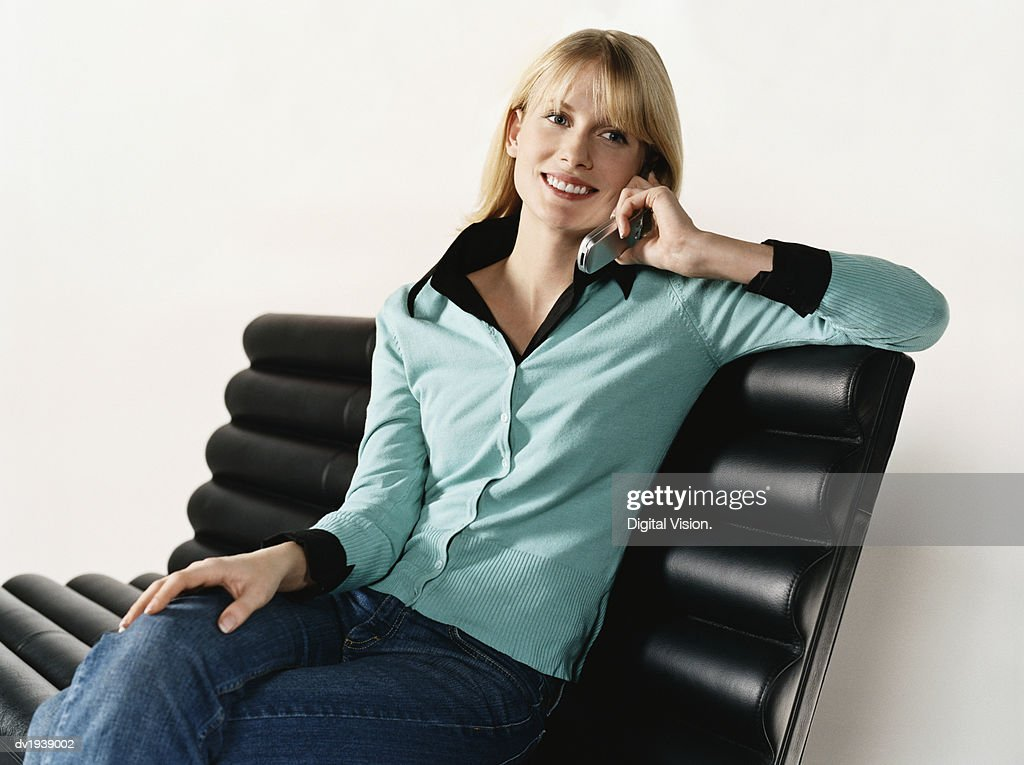 Woman Sits on a Bench, Talking on Her Mobile Phone : Stock Photo