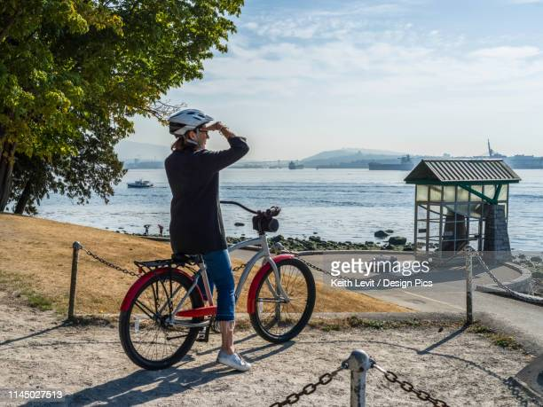 a woman sits on a bike looking out to the ocean and coastline at the stanley park seawall - seawall stock pictures, royalty-free photos & images