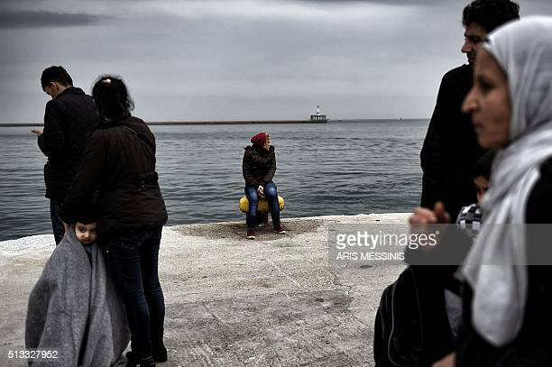 TOPSHOT A woman sits on a bollard in a harbour as migrants and refugees arrive on the Greek island of Lesbos while crossing the Aegean Sea from...