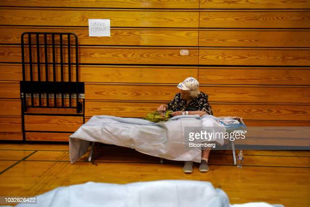 A woman sits on a cot after being evacuated at Southeast Raleigh High School ahead of Hurricane Florence in Raleigh North Carolina US on Wednesday...