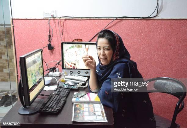 A woman sits on a desk in Balochistan's first women run restaurant in Quetta Pakistan on October 25 2017 Hamida Ali Hazara owner of Balochistan's...