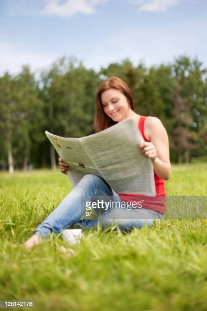 Woman sits on a grass and reads the newspaper