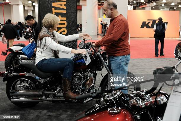 A woman sits on a Harley Davidson motorcycle on the floor at the Progressive International Motorcycle Show at the Javits Center on December 1 2017 in...