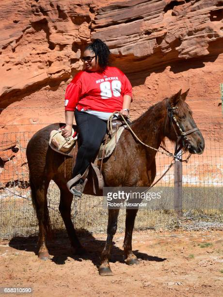A woman sits on a horse at a rest stop during a horseback tour at Canyon de Chelly National Monument near Chinle Arizona Tourists can visit the...