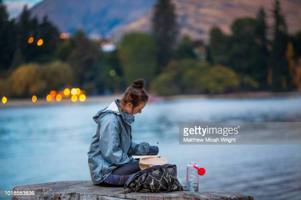 a woman sits on a log lakeside in queenstown on the edge of lake wakatipu and writes in her diary. - matthew hale stock pictures, royalty-free photos & images